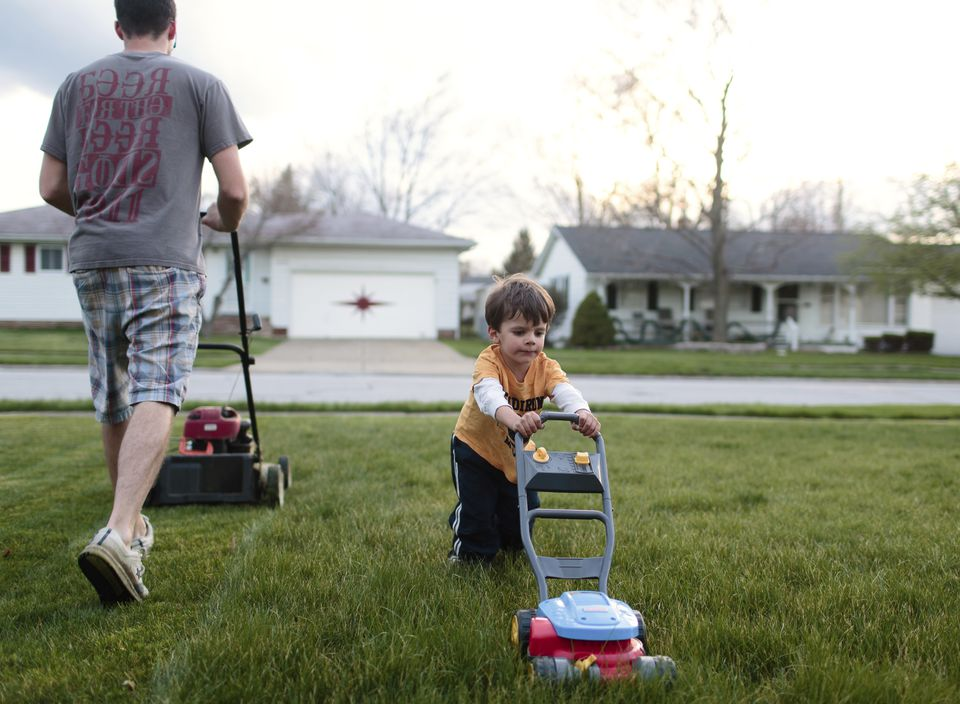 A child, boy pretending to mow the lawn next to a man, father mowing the lawn in a suburban environment.