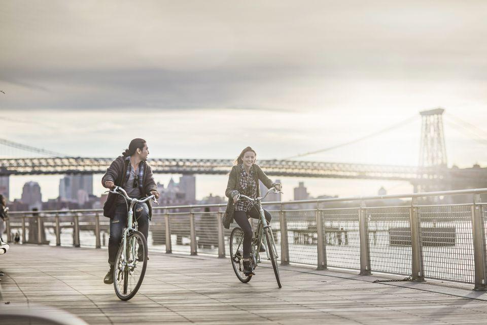 Couple riding bicycles against Williamsburg Bridge