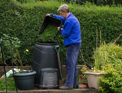 Man filling compost bin in garden