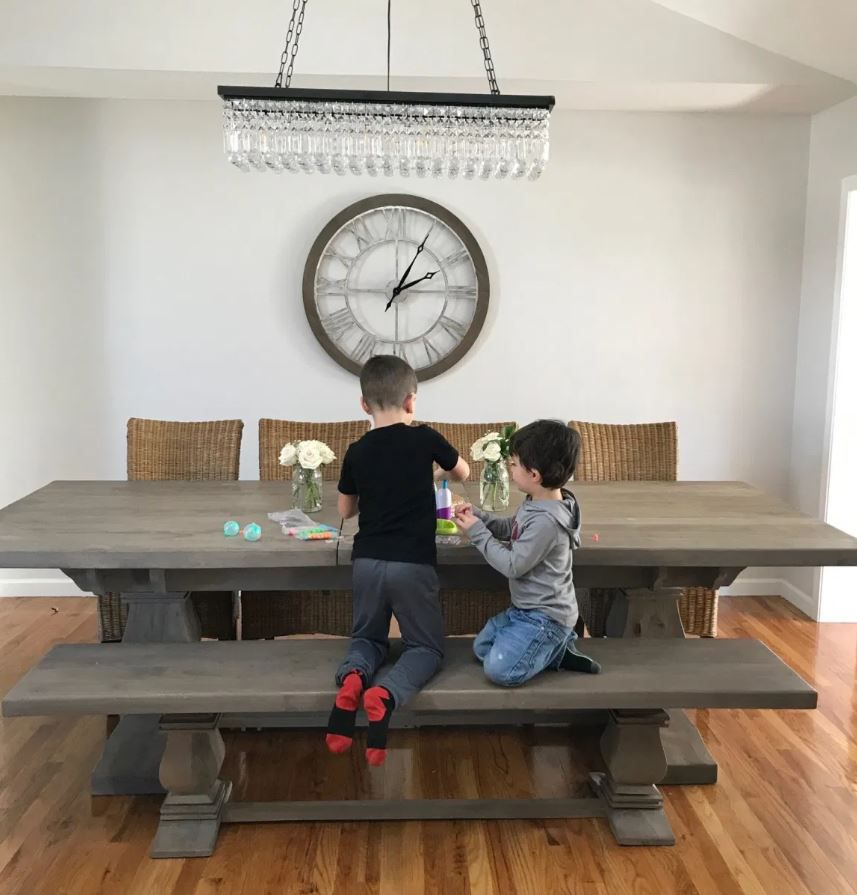 Dining room with wood floors, large chandelier, and large clock on wall.