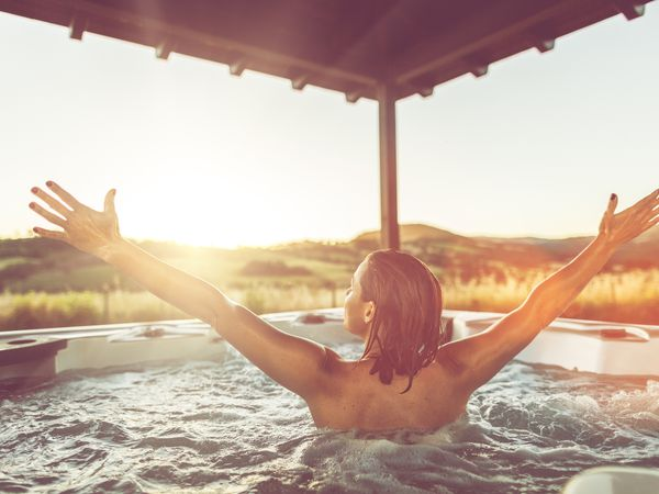 A girl raising her hands in the hot tub overlooking hills.
