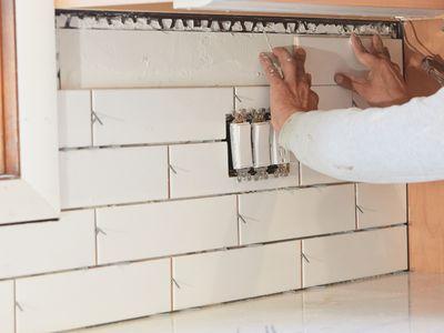 White tile backsplash being installed for kitchen remodeling