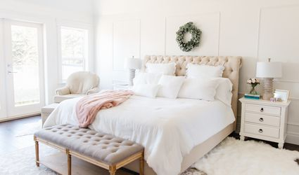 White bedroom tufted bed with wreath above