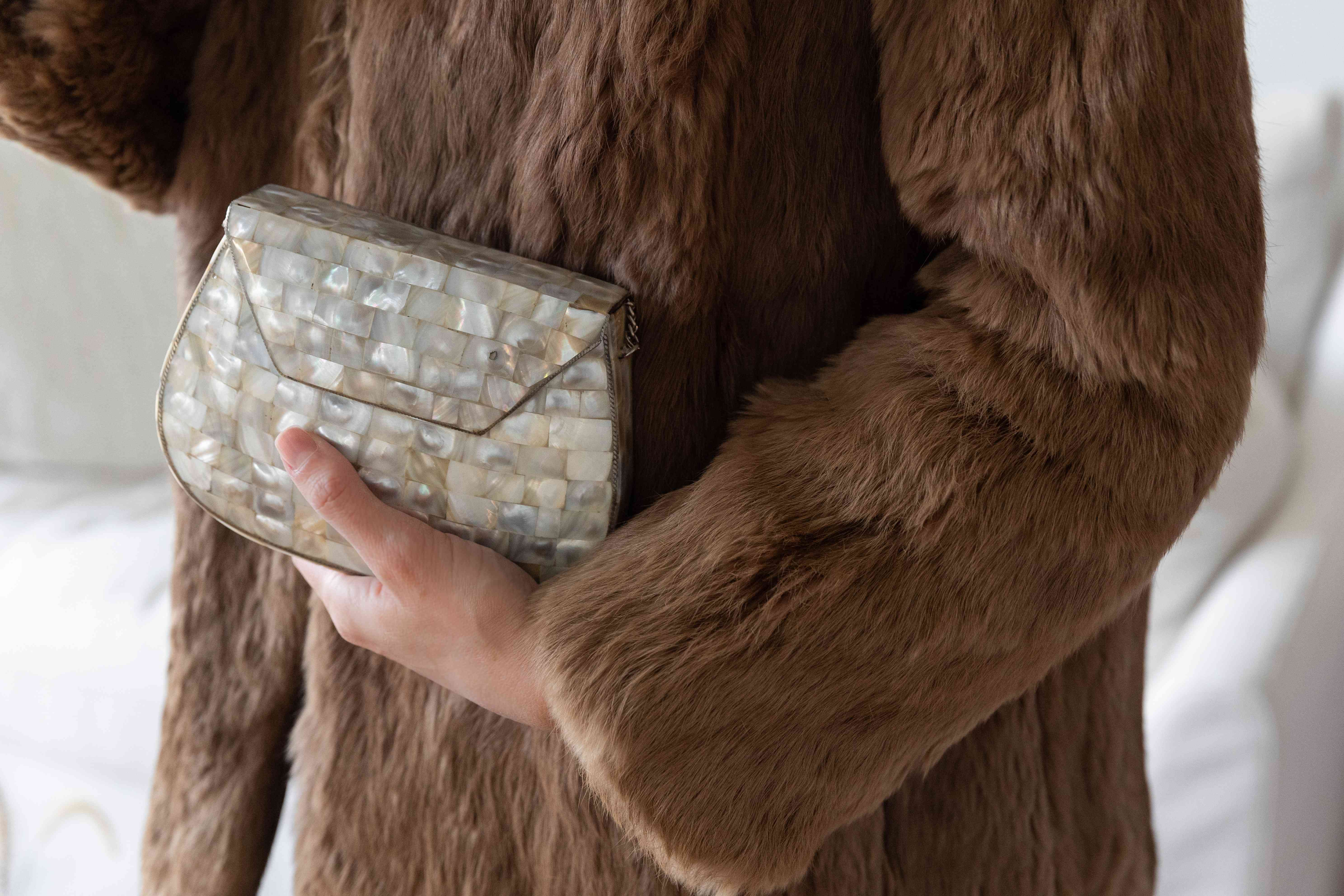 Someone wearing a brown fur coat and holding a clutch purse