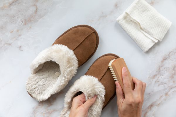 person cleaning suede slippers