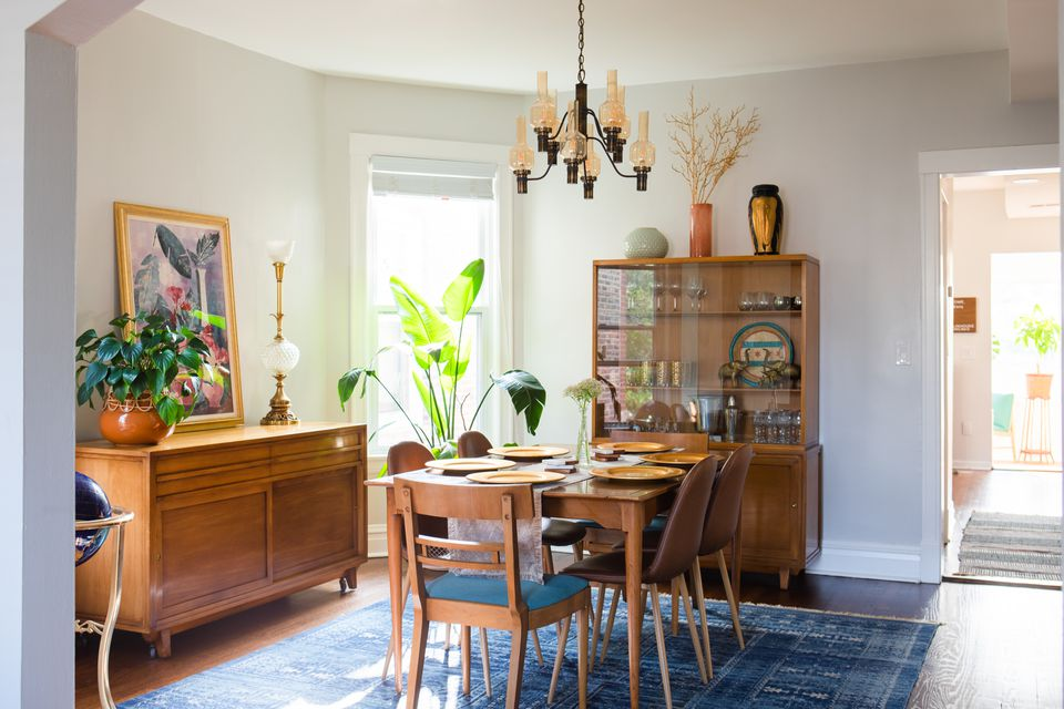 Dining room with wooden furniture, hanging chandelier and bird of paradise plant by sunny window