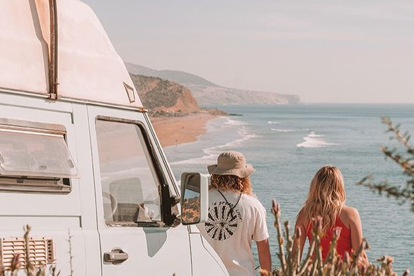 A couple looking out over the coast with their van behind them