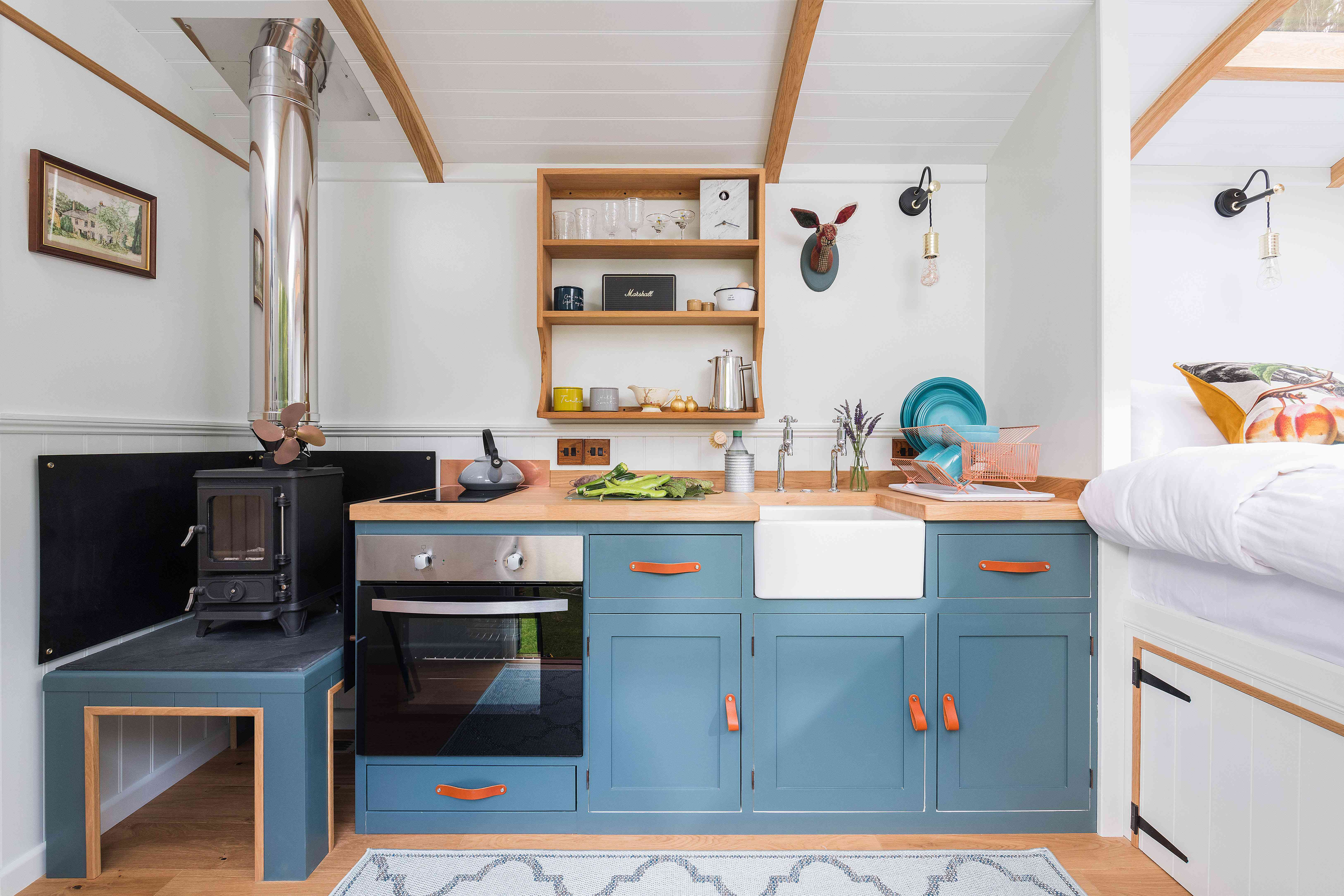 Tiny house kitchen with bright blue cabinets and leather hardware