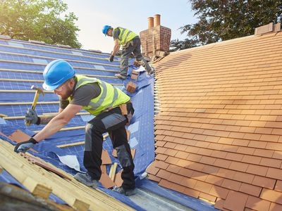 A roofer nails new roof tiles
