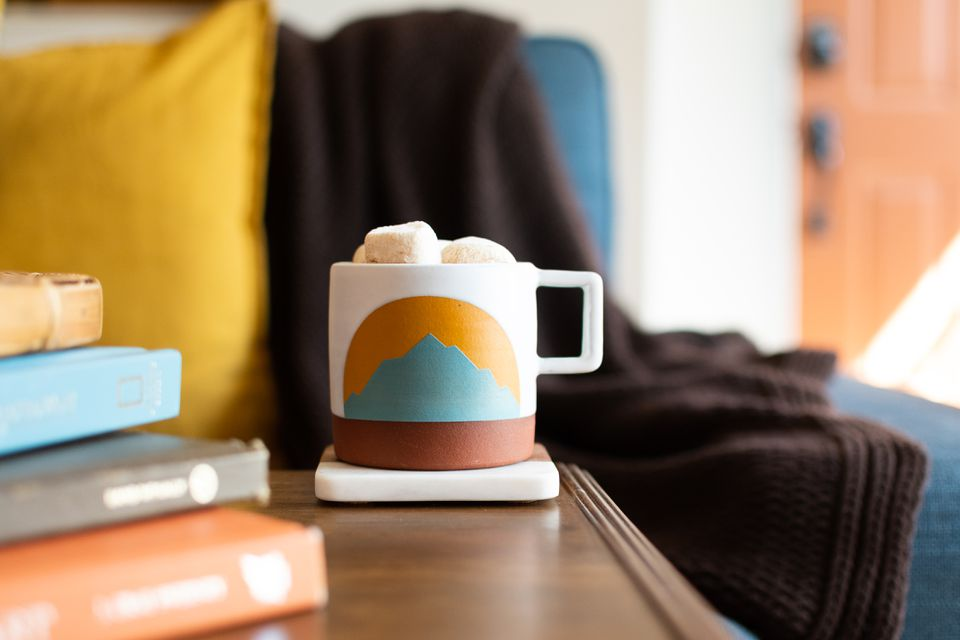 Mug with marshmallows and painted mountain-scape on side next to stacked books