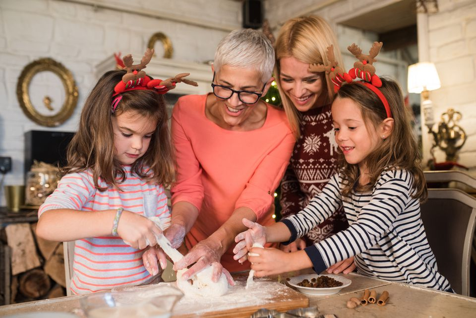 Grandma, mother, and daughters baking Christmas cookies