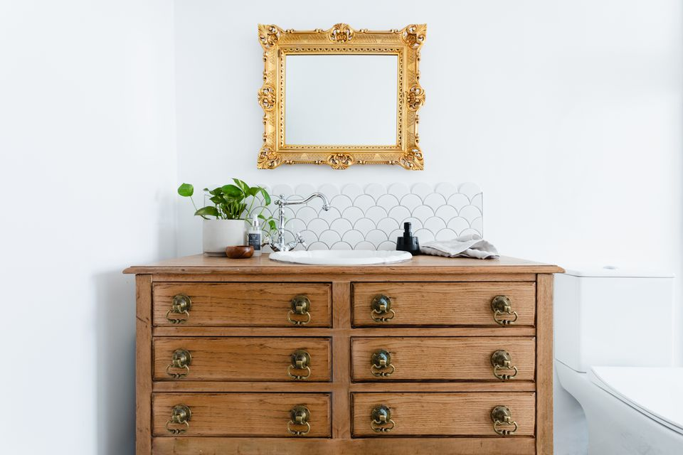 Upcycled wooden dresser used in bathroom as sink below gold framed mirror