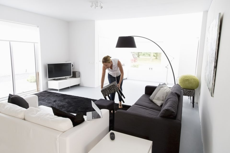 Lady cleaning a white living room