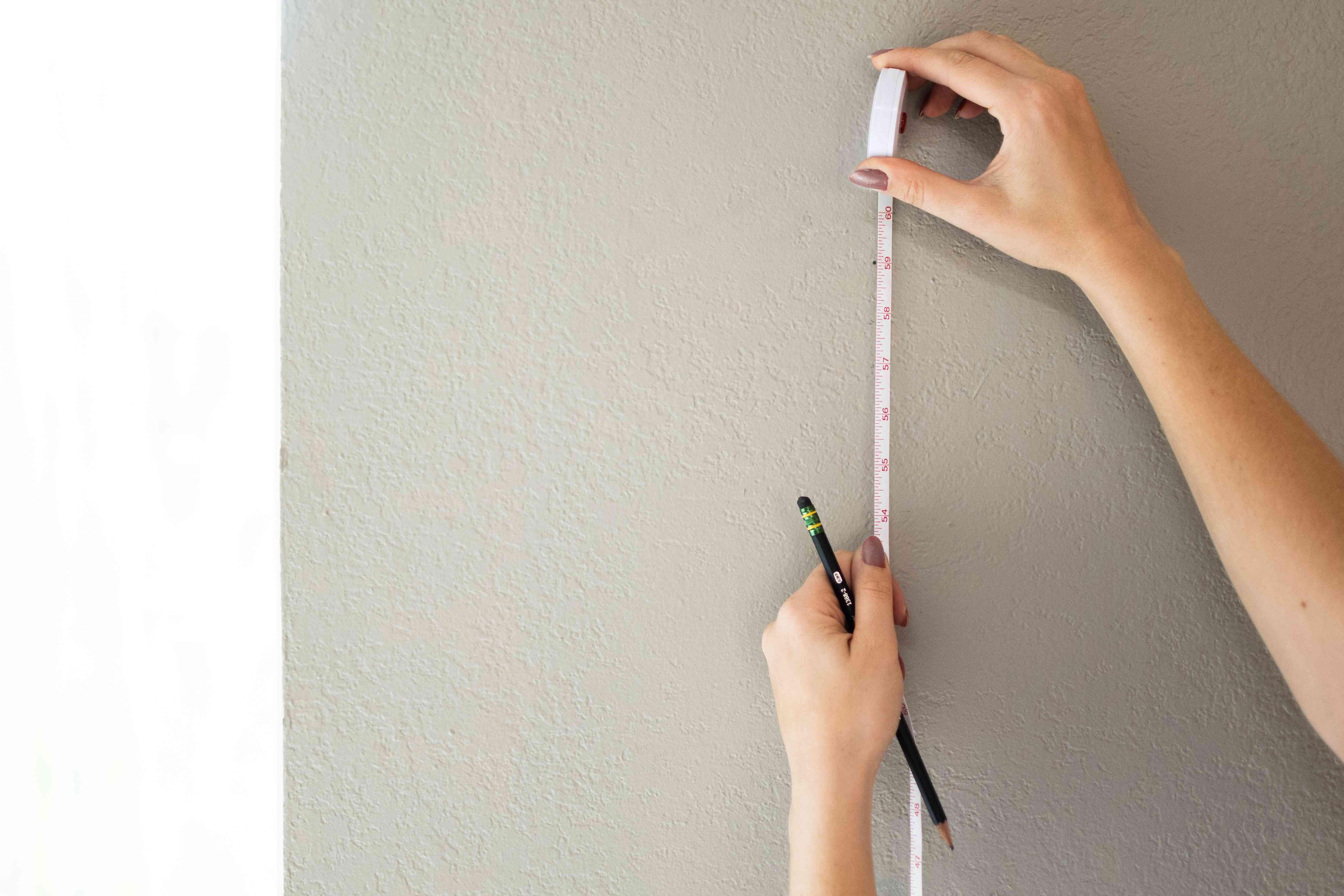 White tape measure determining center mark for frame on wall