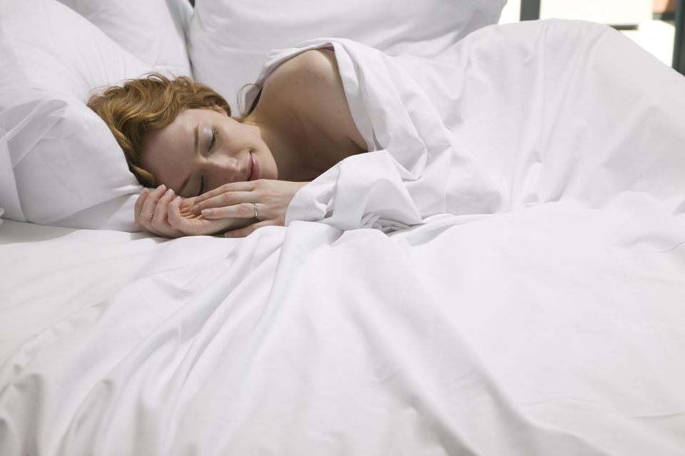 Woman napping in all-white bed sheet bed.