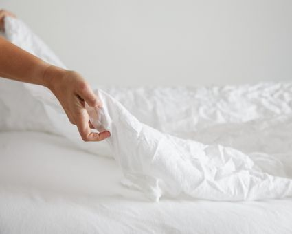person putting on bed sheets