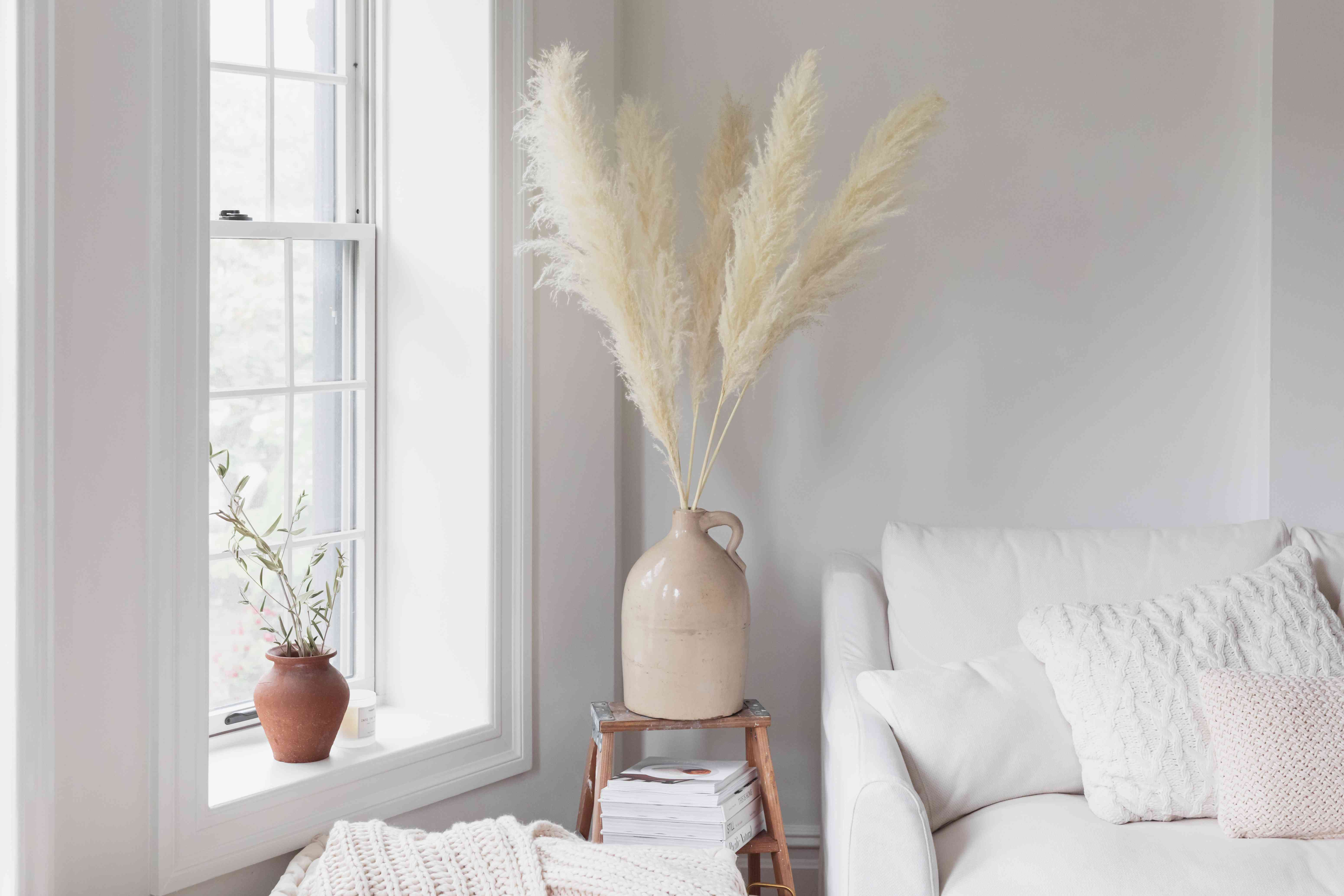 Cream-colored pampas grass in beige ceramic vase in room corner next to window and white chair