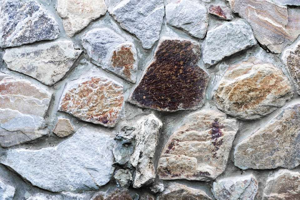 Natural stone wall with different size of rocks. Rustic stone veneer in shades of brown and beige; Wall covering with natural stones