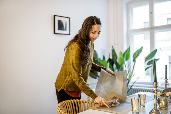 Woman arranging dining table for dinner party