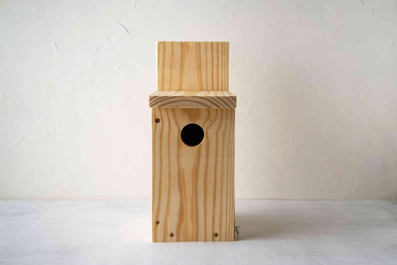 An unpainted birdhouse.