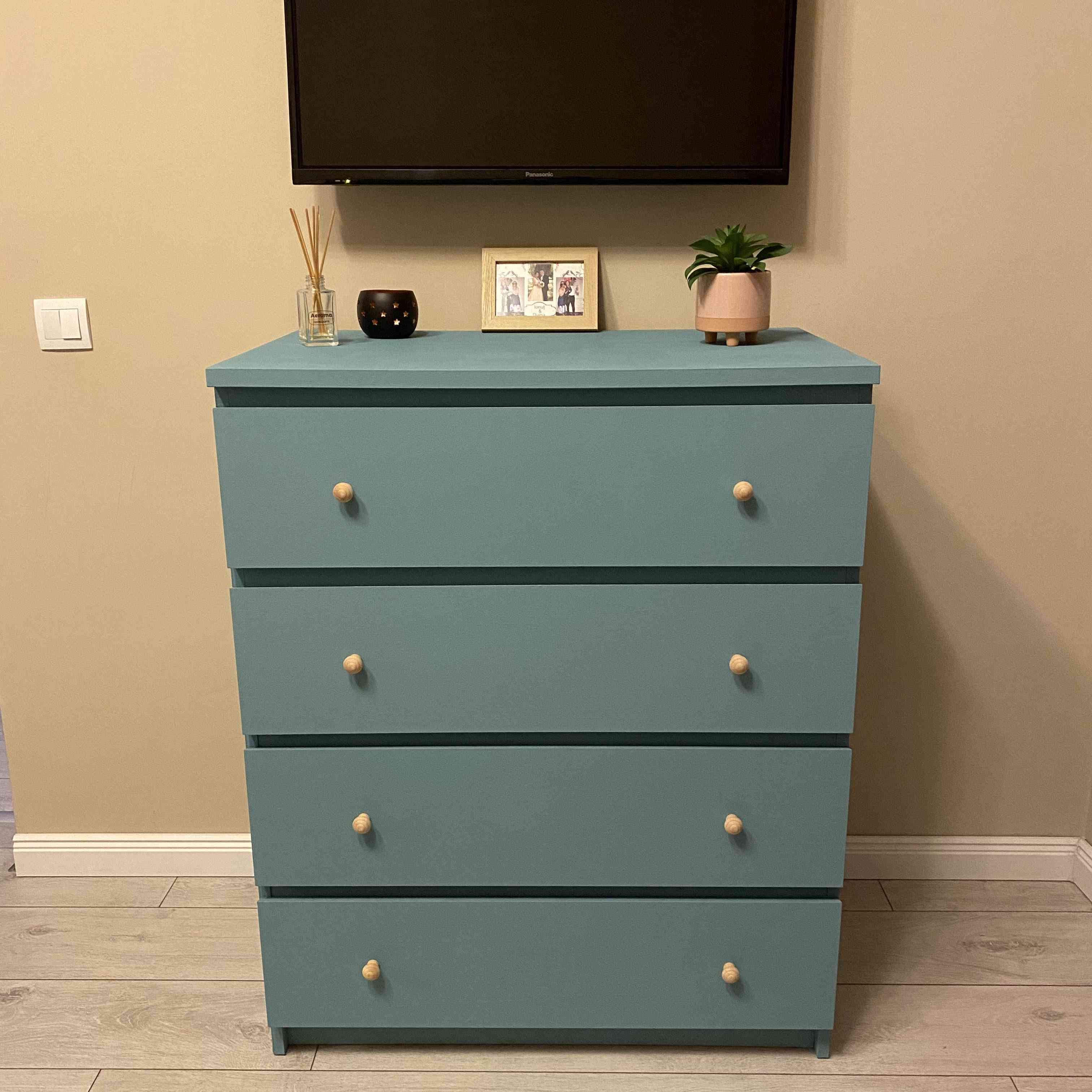 four-drawer malm dresser painted blue-green with wooden knobs