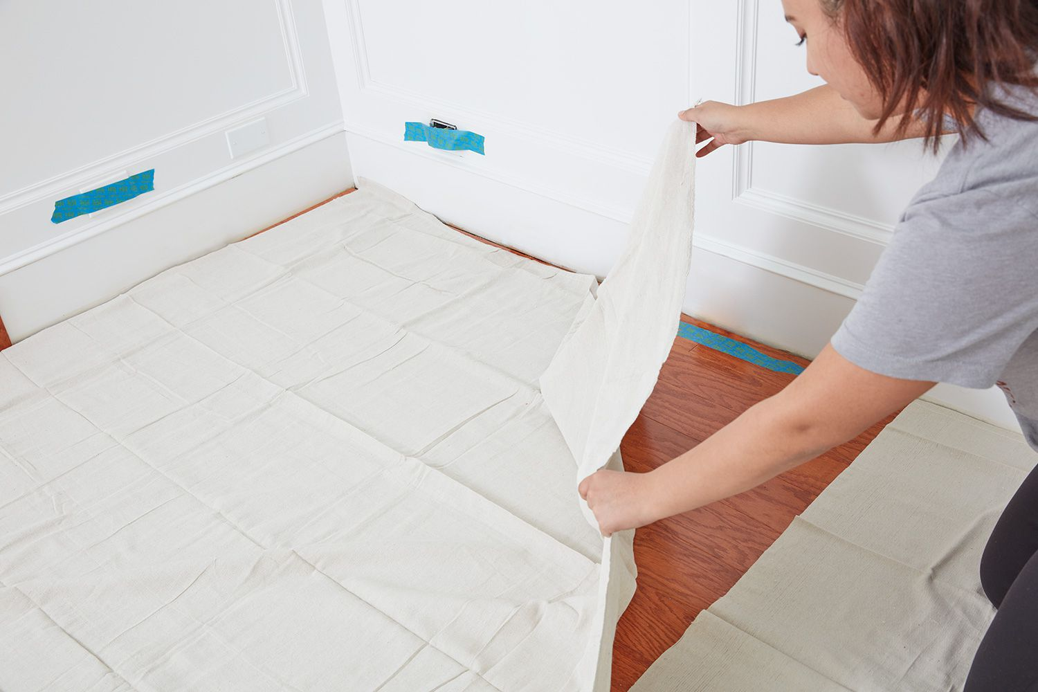 Woman laying drop cloth before painting