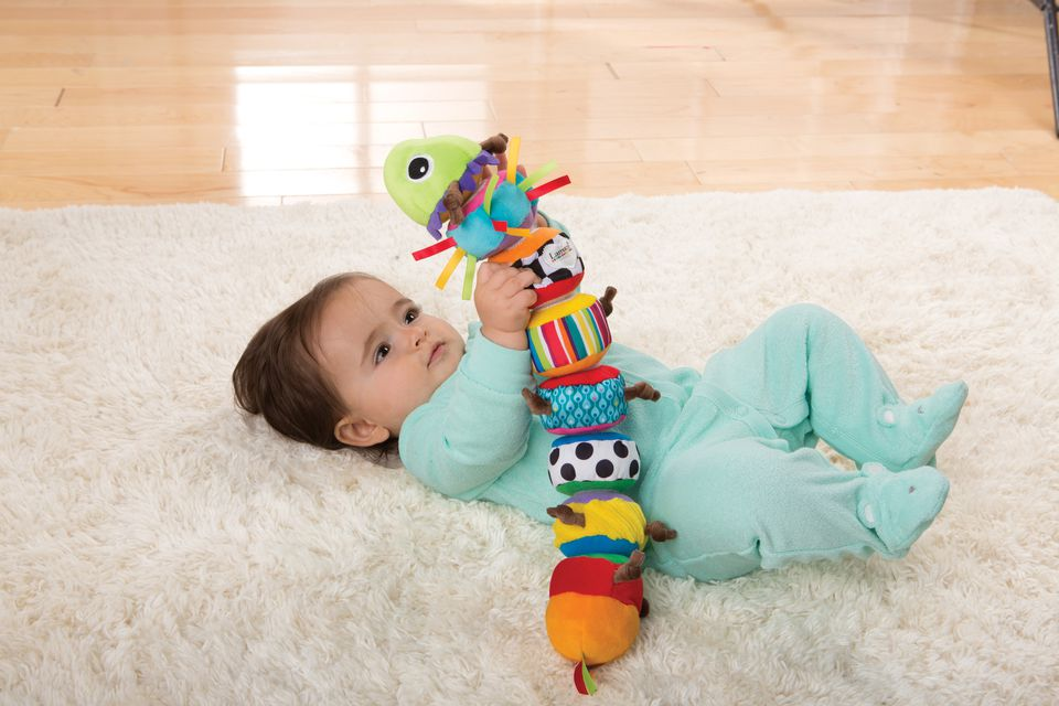 Baby plays with a Lamaze caterpillar toy