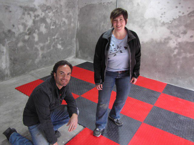Two people installing rubber basement flooring