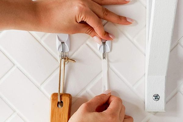 Woman's hand removing Command Strip from tile wall