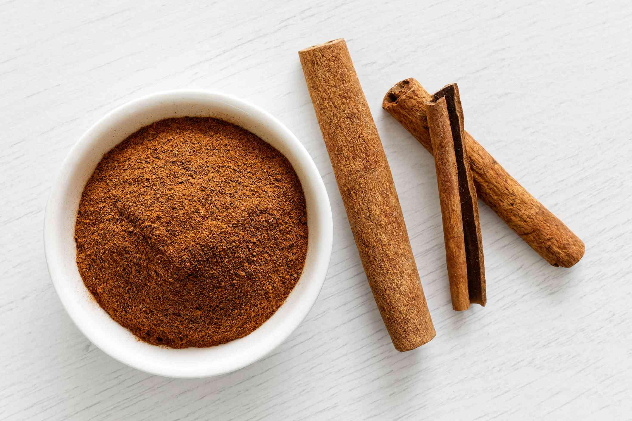 Finely ground cinnamon in white ceramic bowl isolated on white wood background from above. Cinnamon sticks.