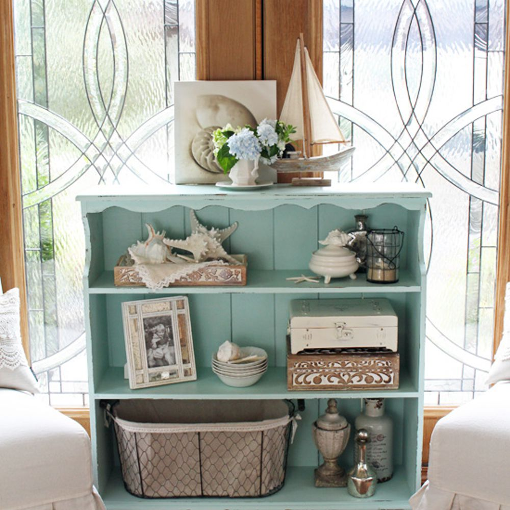 Thrift store bookcase updated with DIY chalk paint adorned with knickknacks.