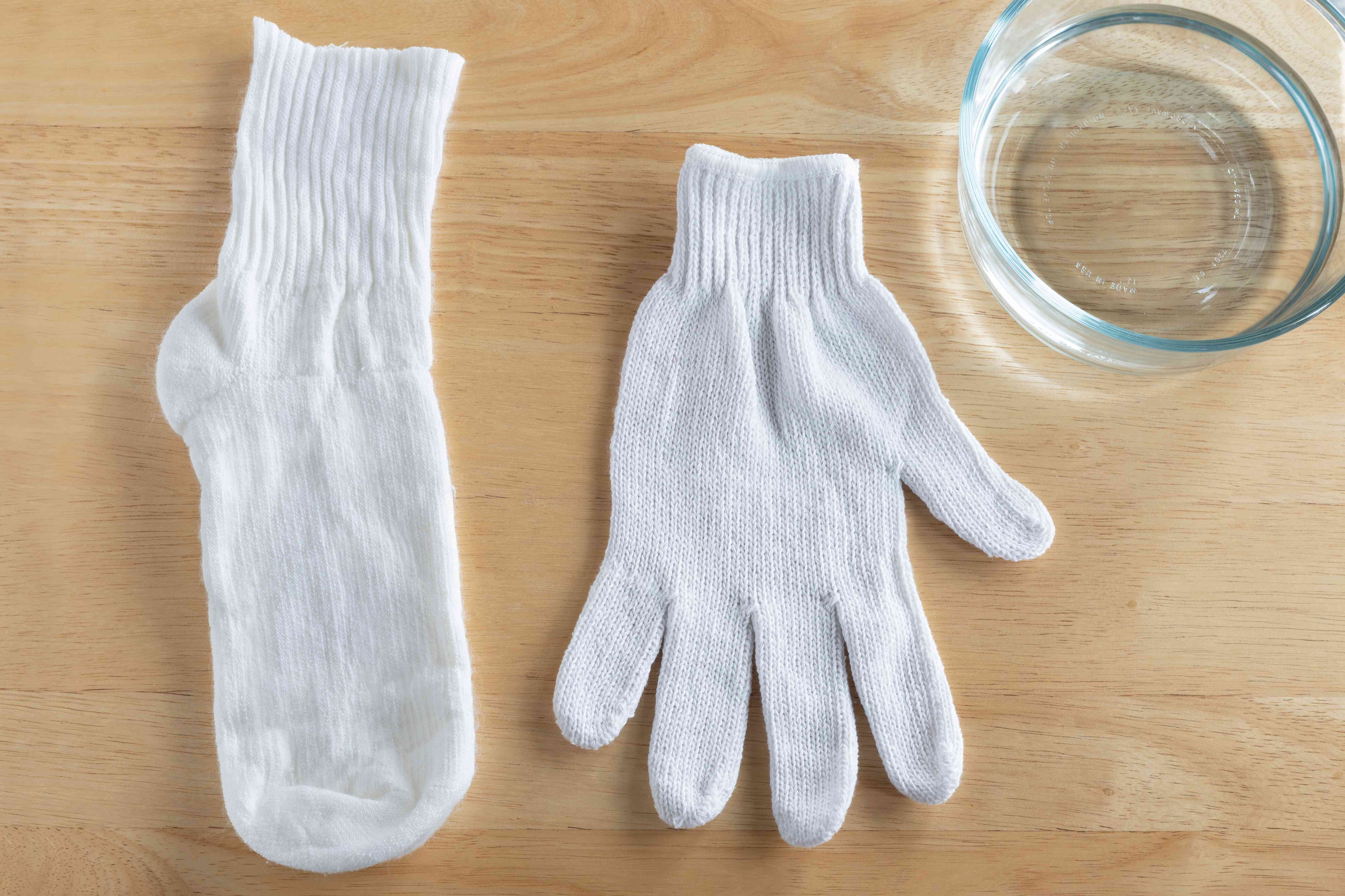 Old glove and white socks next to glass bowl with white vinegar materials