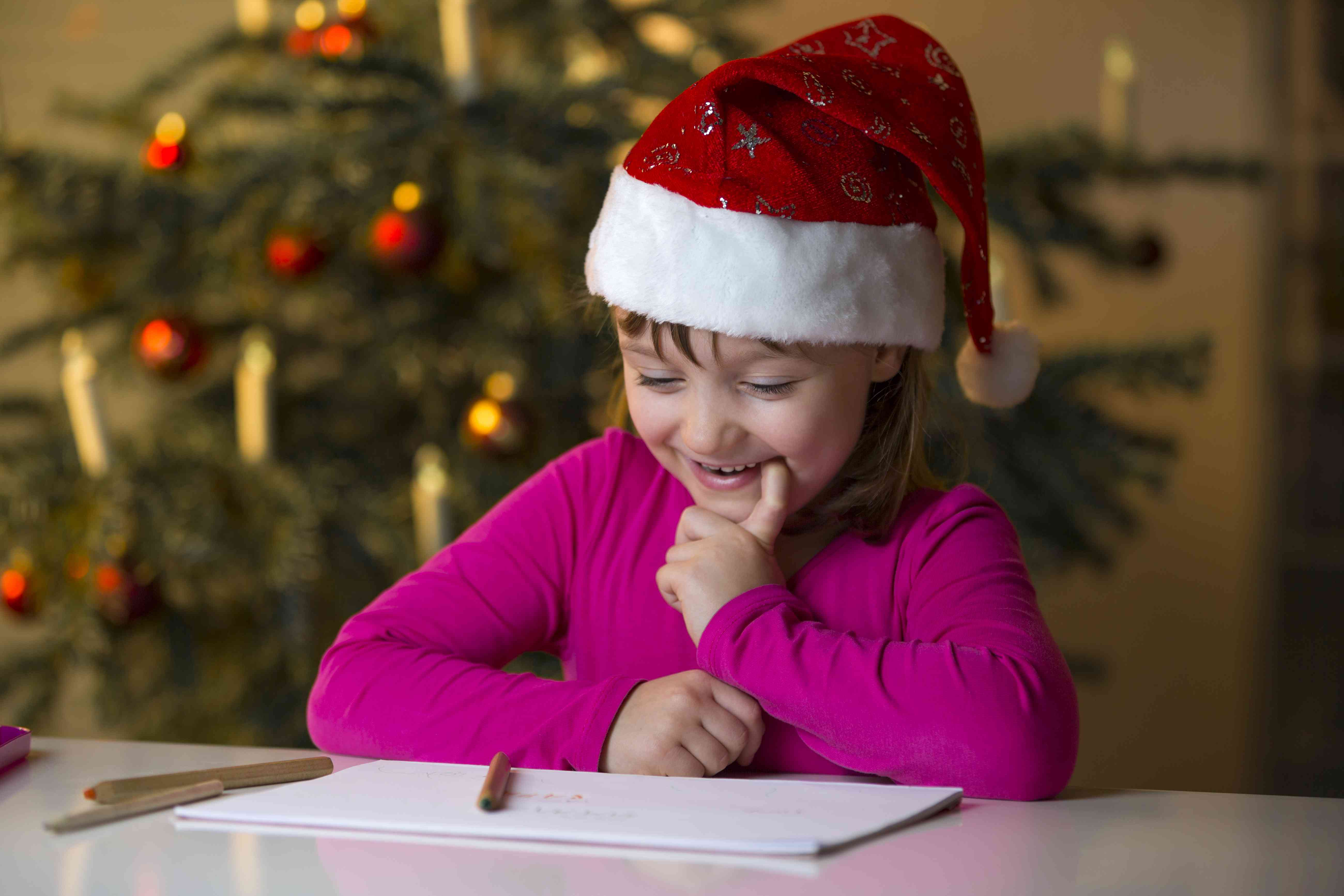 Little girl with Christmas cap looking at her Christmas list