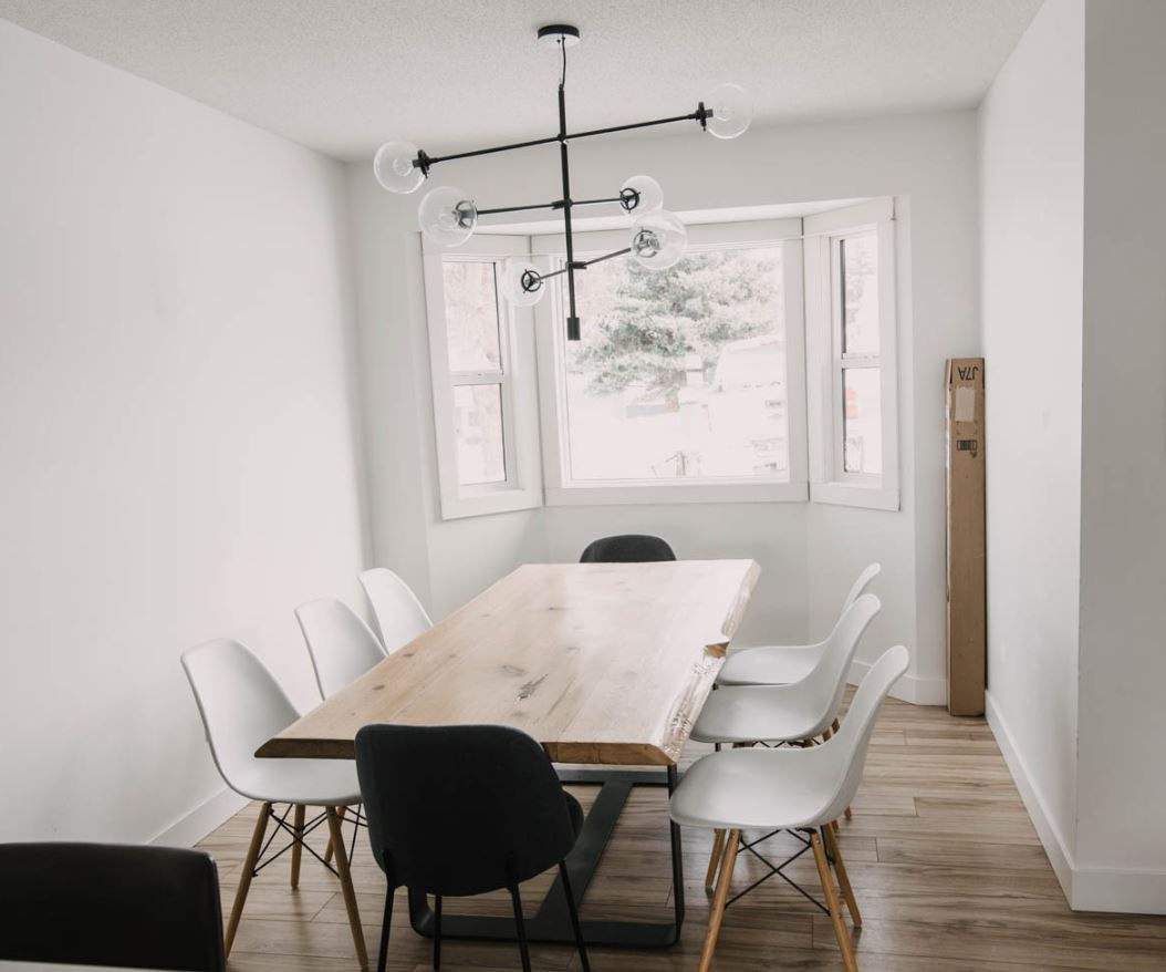 Bare and modern dining room with just table, chairs, and light fixture.