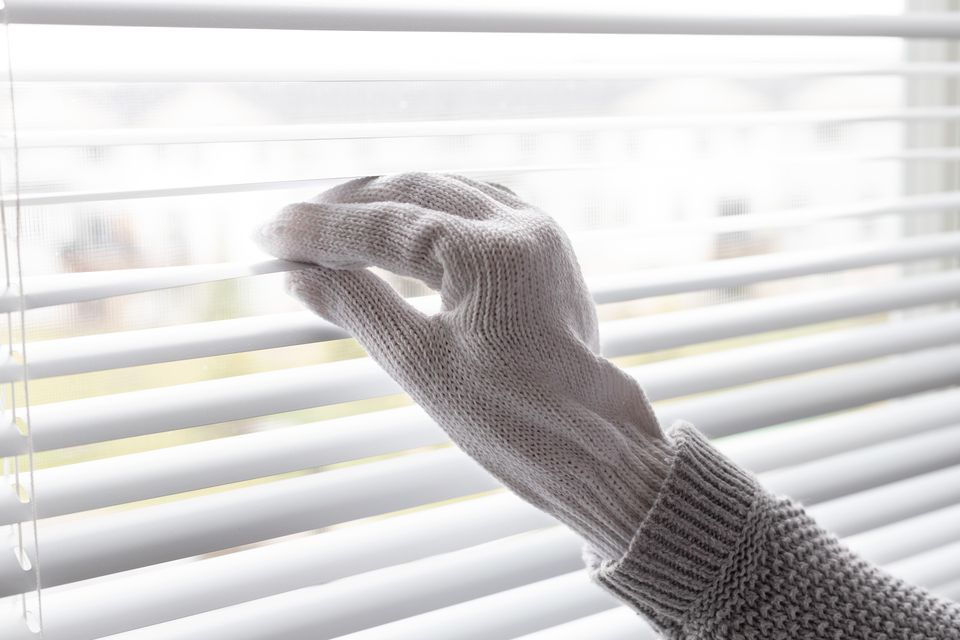 Window blinds held by hand with cotton glove for cleaning