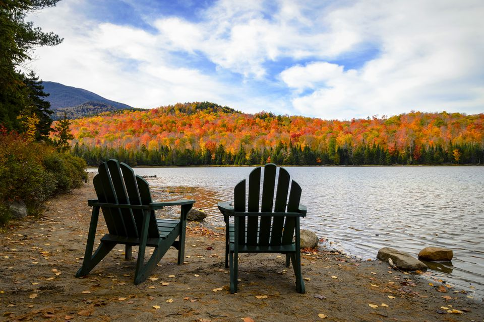 Adirondack chairs by a river in autumn