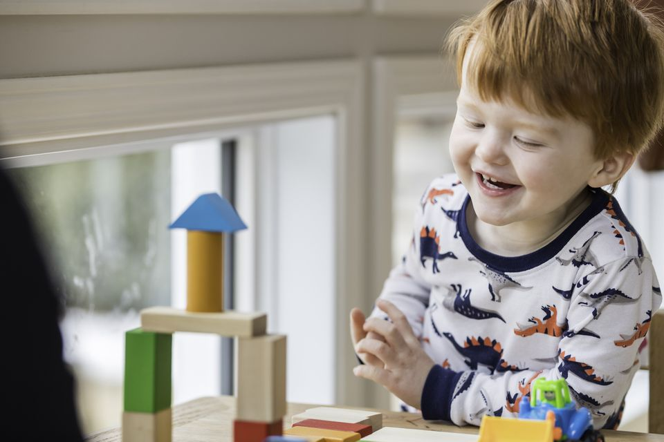 Red headed 3-year-old boy plays with blocks