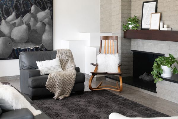 Gray living room with wooden rocking chair and black leather loveseat with throws and pillows on top