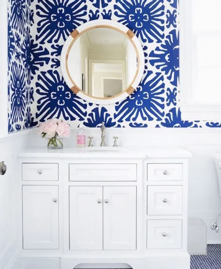 Bathroom with blue and white wallpaper and white vanity.