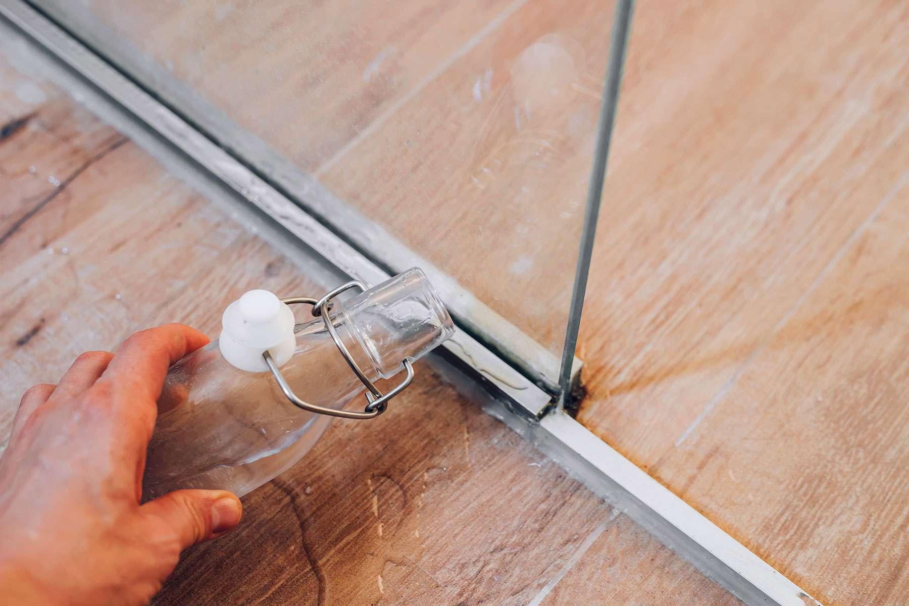 Glass shower door tracks covered with distilled white vinegar
