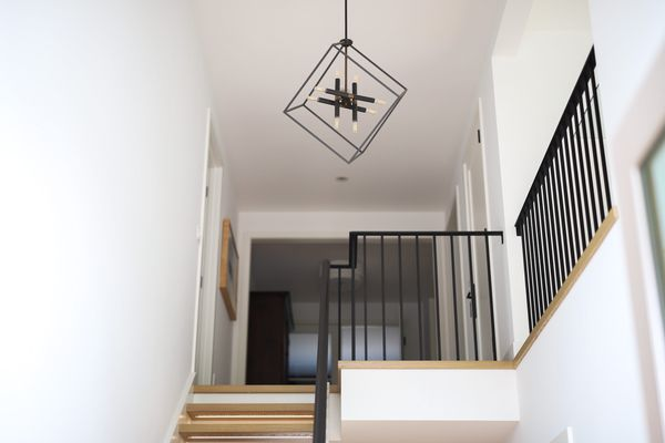 Foyer chandelier with geometric designs over black railing near staircase