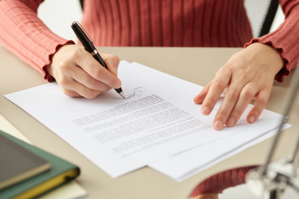 closeup of woman signing a lease