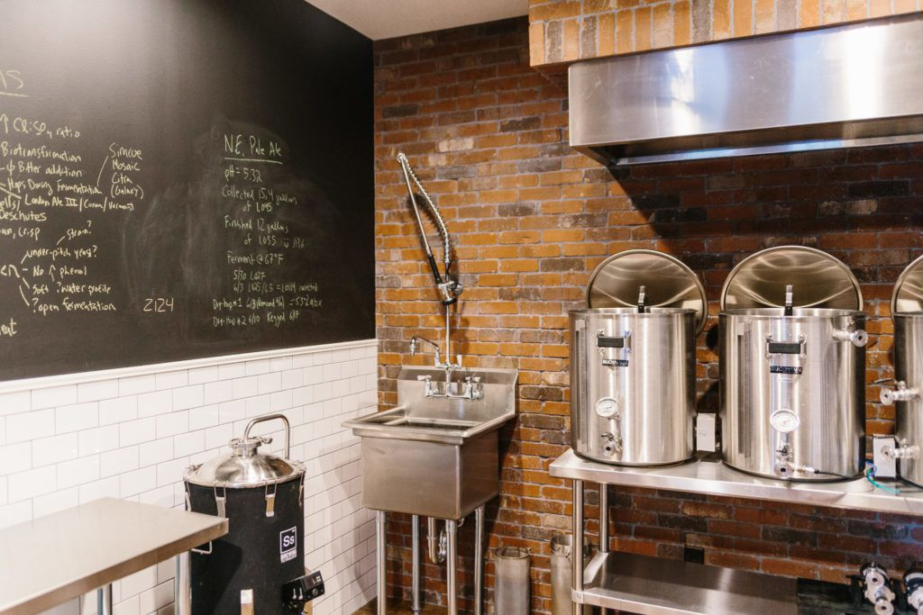 Beer brewing equipment against a brick wall.