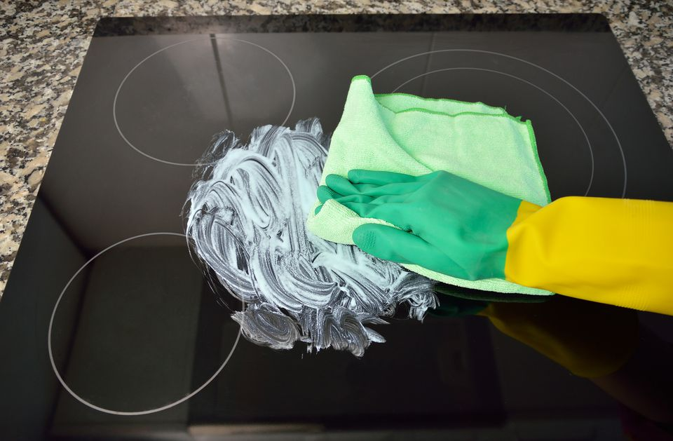 Gloved hand using green cloth to clean glass cooktop