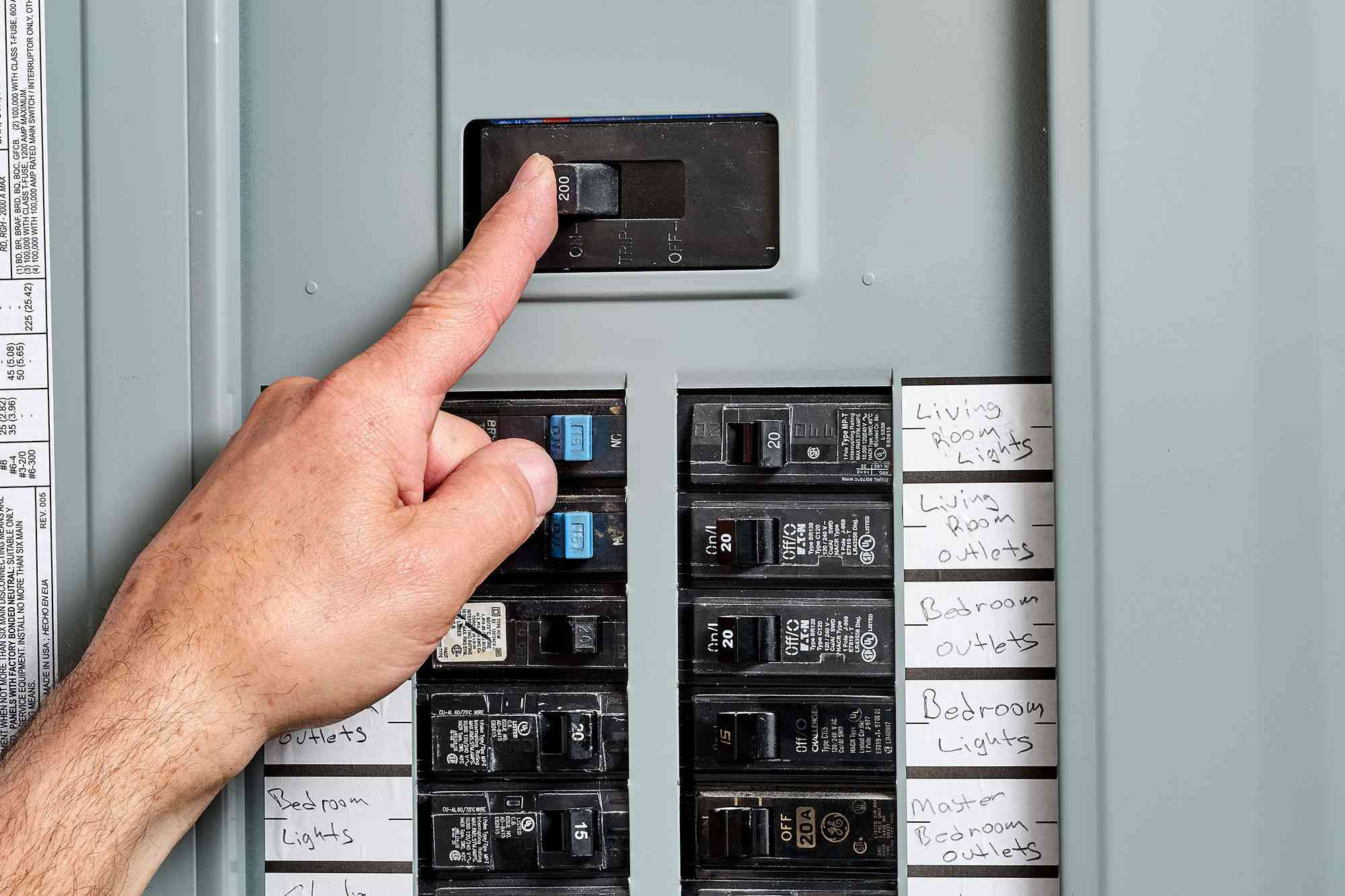person switching off the main power service before beginning work