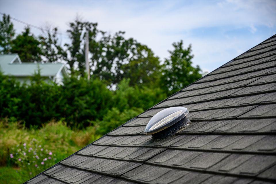 Dome shaped solar tube skylight on asphalt shingle roof