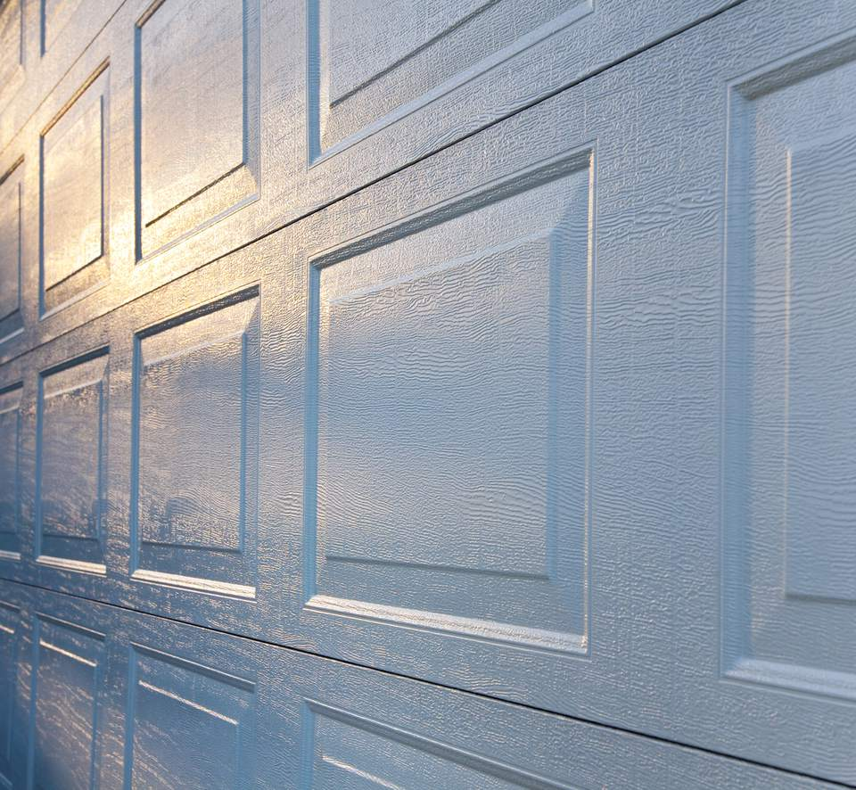 New Aluminum Garage Door Background; Textured Surface Reflecting Sunrise