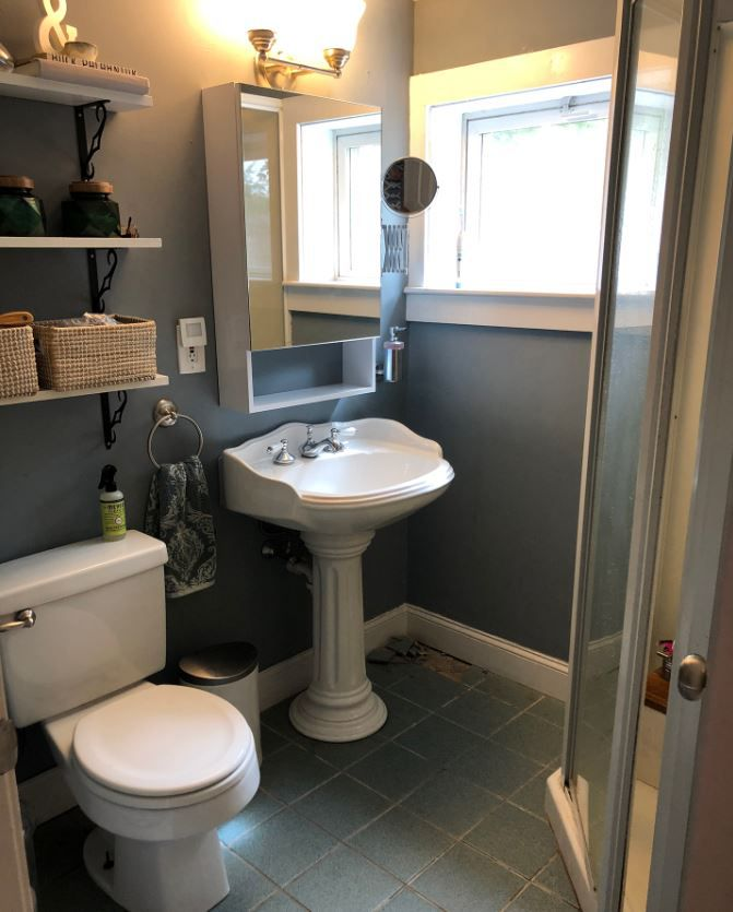 Small bathroom with dark gray walls and white pedestal sink.