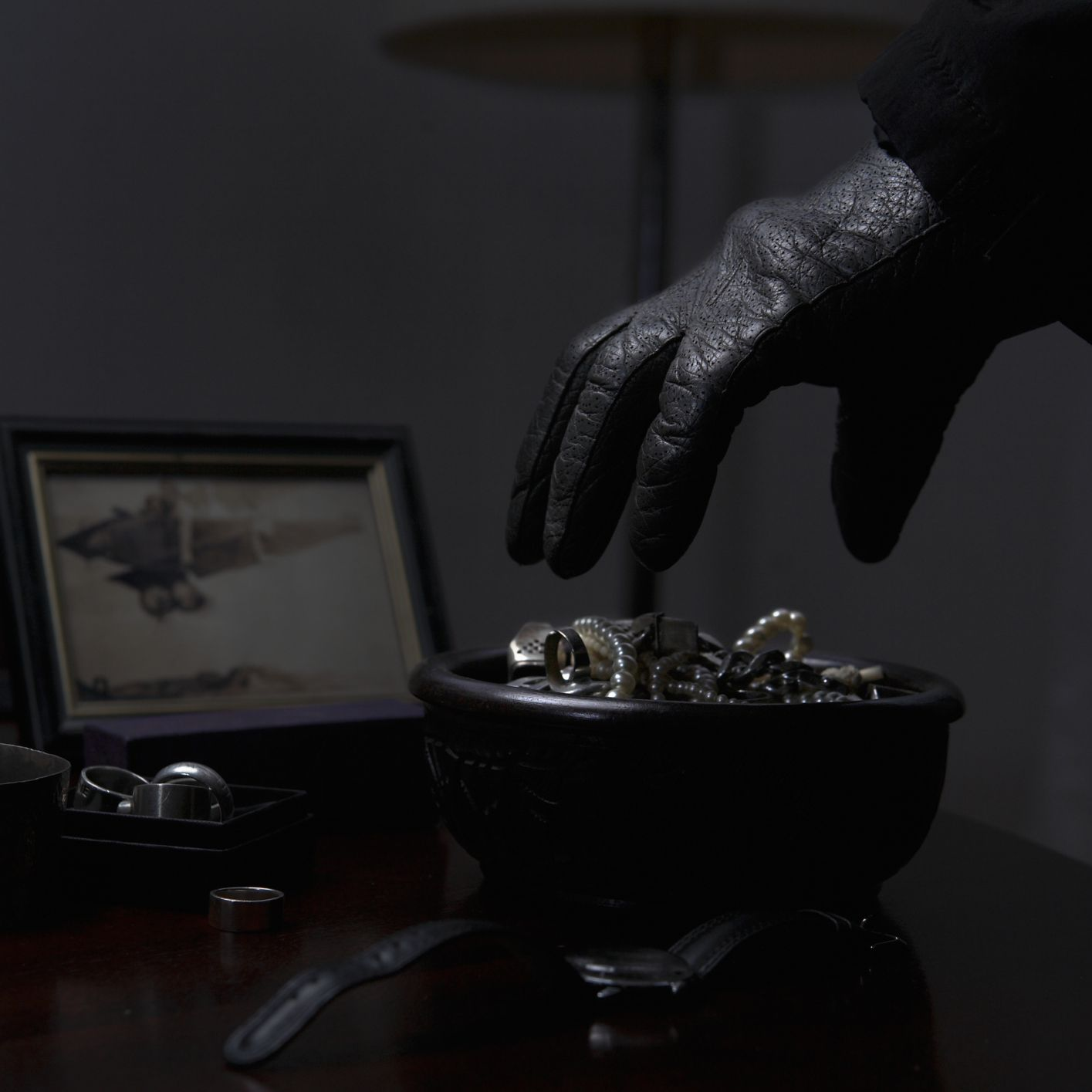 gloved hand reaching for jewelry
