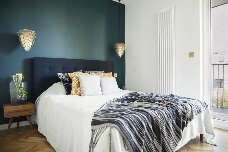 Stylish and modern sunny bedroom interior with small wooden night table , garden in a jar, white bedding, colours pilows and blanket. Space with blue walls and brown wooden parquet.